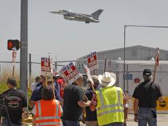 An F-16 takes off as members of International Association of Machinists & Aerospace Workers 776 picket at the Lockheed Martin gate in White Settlement, Texas, April 23, 2012. The union overwhelmingly rejected the company's final contract offer Sunday, initiating a strike.
