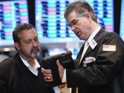 A trader, right, works on the floor of the New York Stock Exchange in New York City.