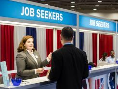 Elizabeth Fahey talks with a job seeker at the Military Officers Association of America career fair April 24, 2012 in Washington, DC.