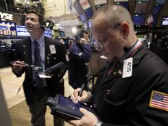 Robert Arciero, right, works with fellow traders on the floor of the New York Stock Exchange on Monday.