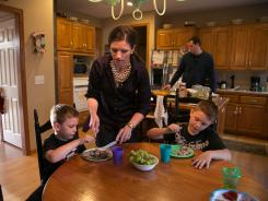 Amber Young at home with her husband Bill and sons Cameron, 6, and Brody, 8, as she prepares dinner.