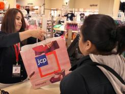 Lisette Barraza hands a shopper her merchadise in a bag displaying the new store logo at a JCPenney store in the North Riverside Park Mall in Illinois Feb. 1, 2012.