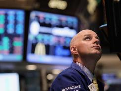 A trader works on the floor of the New York Stock Exchange April 25, 2012.
