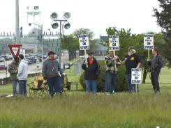 Union members strike Tuesday outside Caterpillar's plant in Joliet, Ill.