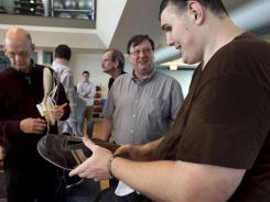 Igor Vovkovinskiy speaks Thursday with Trevor Kirby, center, a shoe engineer at Reebok headquarters in Canton, Mass.
