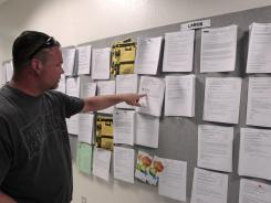 Tom Holloway looks for work at a sign board at JobTrain, an employment center, in Menlo Park, Calif., April 20, 2012.