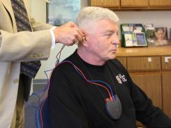 Karl Keul visits with audiologist Dr. Ken Henry to have his hearing checked in Falls Church, Va.