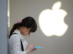 A woman uses her mobile phone outside an Apple store in Shanghai.