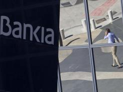A man is seen reflected Wednesday in the glass building of the Bankia bank headquarters in Madrid.