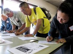Job candidates fill out forms for employment interviews at a job fair in Bell, Calif., March 9, 2012.