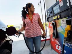 Carlin Malina pumps gas at a Ugas station April 24, 2012 in Miami. A drop in gasoline prices helped keep wholesale prices down.