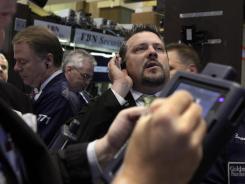 Trader Jason Harper, right, works on the floor of the New York Stock Exchange.