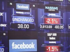 Electronic screens at the Nasdaq stock market announce the listing of Facebook shares before the start of trading, May 18, 2012 in New York.