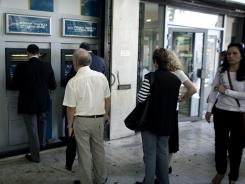 People withdraw money from a branch of the National Bank of Greece in central Athens May 17, 2012.