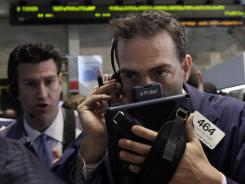 Trader Gregory Rowe, right, works on the floor of the New York Stock Exchange.