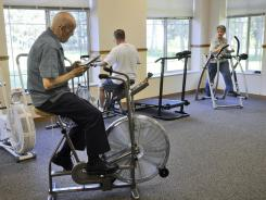 From left, Dave Simondet, Gary Lerud and Cathy Simondet take advantage of the exercise room at Realife Cooperative at Mueller Gardens in St. Cloud, Minn.