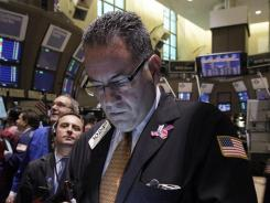 Trader John Vaccarine, right, works on the floor of the New York Stock Exchange in New York, in May 2012.