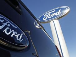 The Ford logo on the tailgate of a pick-up truck and on a dealership sign in Salem, N.H.