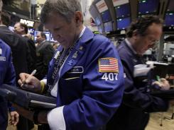 Trader Richard Newman, left, works on the floor of the New York Stock Exchange in April 2012.