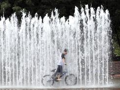 An 8-year-old rides his bike though a fountain in Bristol, Va., in this summer 2010 file photo.
