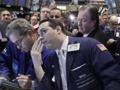 Stock specialist Michael Gagliano, foreground right, works at a post on the floor of the New York Stock Exchange.