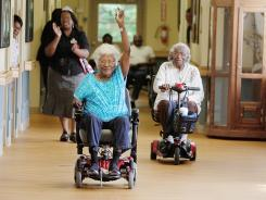 Cebelle Sherrie, left, waves as she passes Mabel Hart during wheelchair races on May 15, 2012, at Rose Manor Healthcare Center in Durham, N.C.