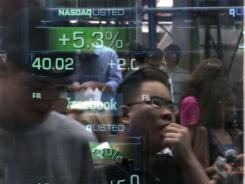 Passers-by are reflected in the Nasdaq media center's window as they view trading activity on Facebook's stock in New York on May 18, 2012.