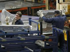 Auto workers at the Ford Stamping Plant in Chicago Heights, Ill., stack a Ford Explorer door panel in April 2012.