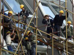 Workers stand on the scaffolding of a modern commercial building in Beijing, China in May 2012.