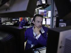 Trading specialist Christopher Trotta is framed by screens as he works on the floor of the New York Stock Exchange on June 1, 2012.