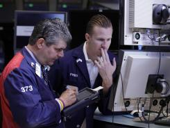 Trader John Panin, left, and specialist Frederick Edwards work on the floor of the New York Stock Exchange on June 1, 2012.