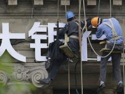 "Workers arrange the Chinese sign of a bank in Shanghai, June 3, 2012 . The Chinese characters read: ""Big bank."""