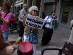 Demonstrators shout slogans against bankers during a demonstration outside a Bankia bank branch in Barcelona, Spain, Friday June 8, 2012.