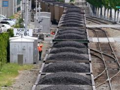 In this May 29, 2012, file photo, a train hauls coal to British Columbia as it heads north out of downtown Seattle.