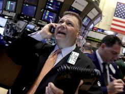 Trader George Ettinger, left, works on the floor of the New York Stock Exchange on June 11, 2012.