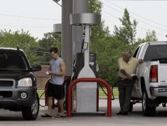 Motorists pump gas under a sign displaying $2.99 for unleaded regular gasoline at a station in North Little Rock, Ark.