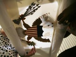 Nereida Rivera, left, and Christine Upchurch hand embroider a vice presidential flag at the Defense Logistics Agency in Philadelphia.
