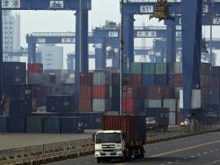 Trucks transport containers at a port in Tianjin, China.