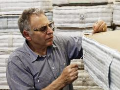 Earl Kluft, who manufactures luxury mattresses, hand-stitches the side walls of an Aireloom handmade bed at his factory in Rancho Cucamonga, Calif.