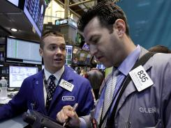Specialist Frank Masiello, left, and trader Glenn Kessler work on the floor of the New York Stock Exchange on Monday, June 11, 2012.