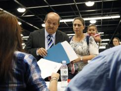 Jose Canales, left, talks to a recruiter at a job fair expo in Anaheim, Calif. in June 2012.