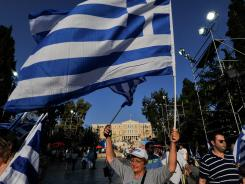 A woman holds a Greek flag in front of the parliament building prior to a speech by New Democracy party leader Antonis Samaras in Athens June 15, 2012.