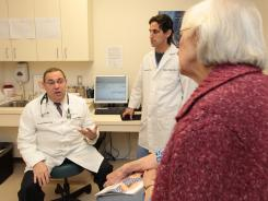 Physicians Kerry Le Benger, left, and Jeffrey Le Benger, center, consult with patient Sheila Chidester in Berkeley Heights, N.J.
