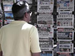 A man reads newspaper headlines in Thessaloniki on Monday, June 18, 2012.
