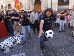 A demonstrator in Rome prepares to kick a soccer ball toward police Thursday during a protest against policies to fight Italy's economic crisis.