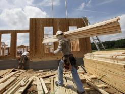 A workman carries a load of wood to a new home to frame a house in Chester , Va., May 16, 2012.