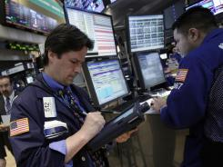Trader Patrick McKeon, left, works on the floor of the New York Stock Exchange in this file photo.