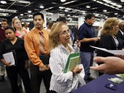 Maria Wilt talks to a recruiter June 13 at a job fair expo in Anaheim, Calif.