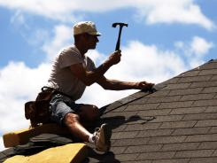 Troy Drake hammers shingles onto the roof of a new house under construction in the Patrick Farms community in Pearl, Miss.