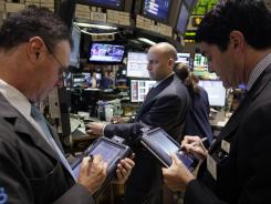 Specialist Meric Greenbaum, center, works at his post on the floor of the New York Stock Exchange on Monday, June 18, 2012.